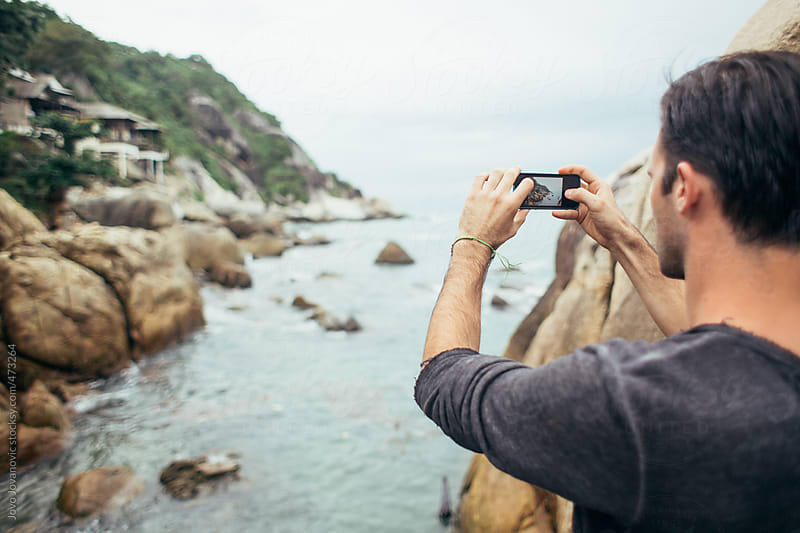 Young man taking photos with his phone with rocky coastline and water in background by Jovo Jovanovic for Stocksy United