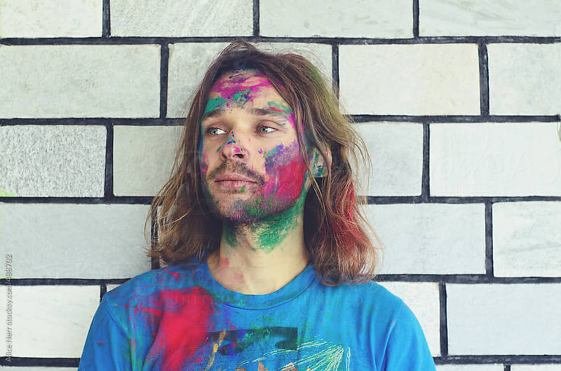 Guy with colorful powder over his face and t-shirt by Alice Nerr for Stocksy United