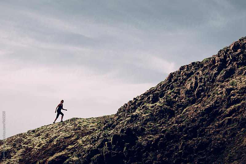 Woman Climbing Mountain Ridge by Evan Dalen for Stocksy United
