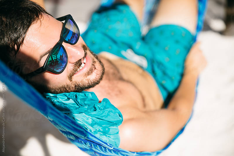 Young man portrait smiling on a hammock in the beach by Alejandro Moreno de Carlos for Stocksy United