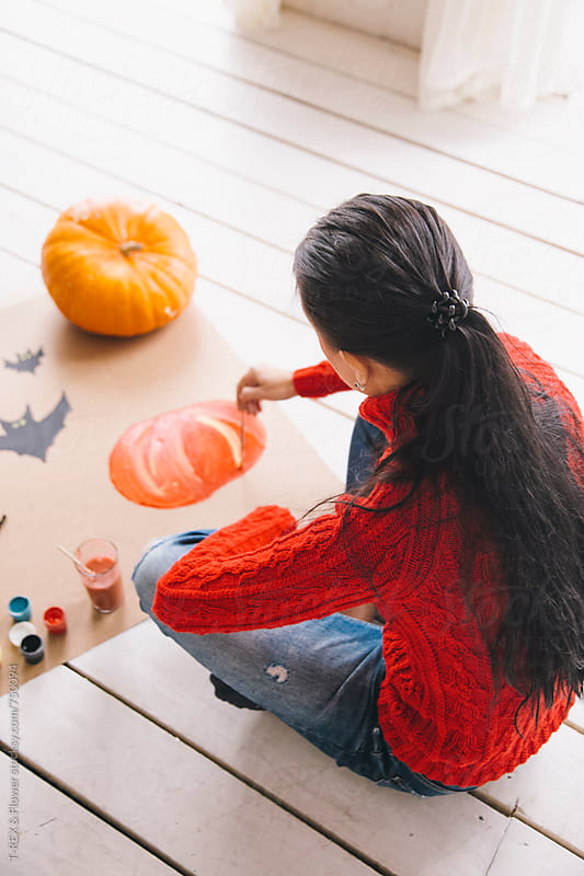 Woman drawing pumpkin with brush and white gouache by Danil Nevsky for Stocksy United