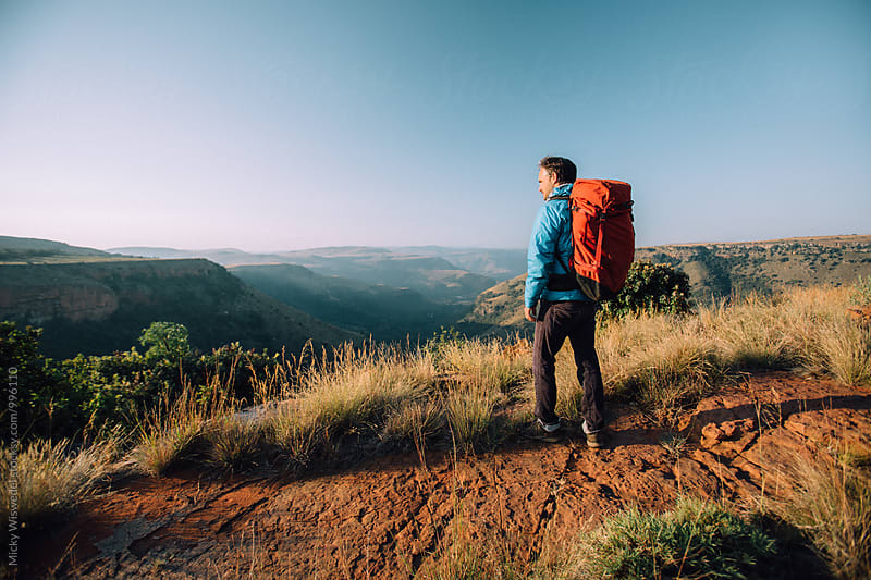 Hiker on a mountain trail overlooking a scenic valley by Micky Wiswedel for Stocksy United