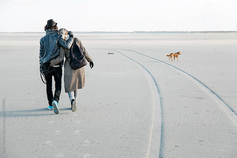 Young happy couple hugging while walking the dog. by Koen Meershoek for Stocksy United
