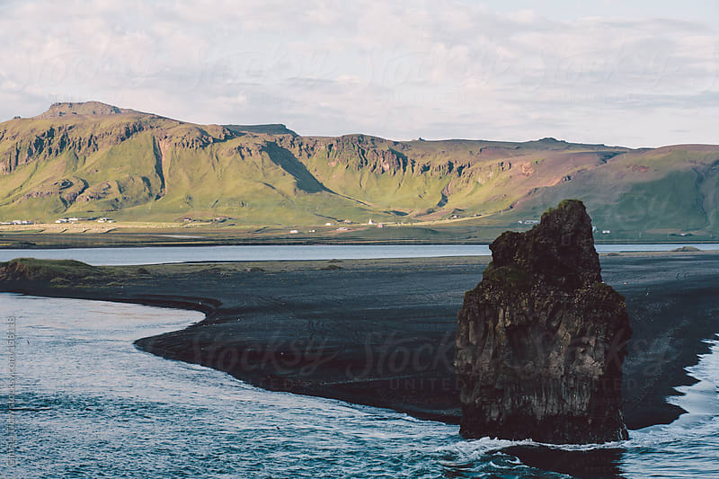 Coastal sunset with huge rock and black sand beach by Gabriel Tichy for Stocksy United