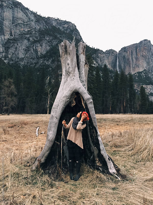 young woman in stump in yosemity by Jesse Morrow for Stocksy United