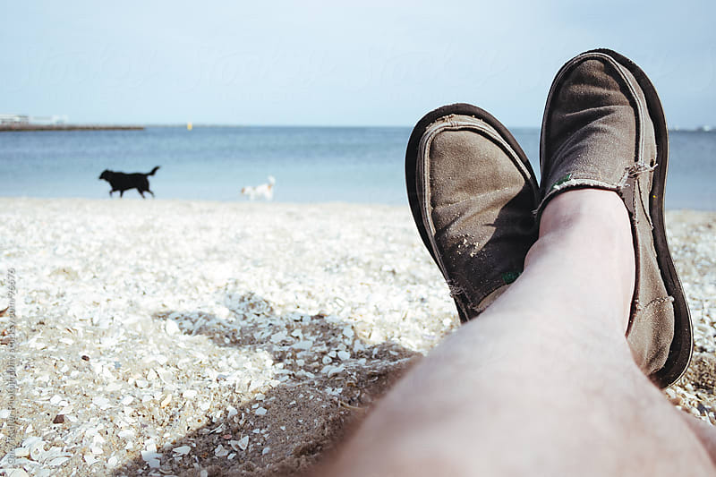 Man's legs on a beach with dogs in background. by Gary Radler Photography for Stocksy United