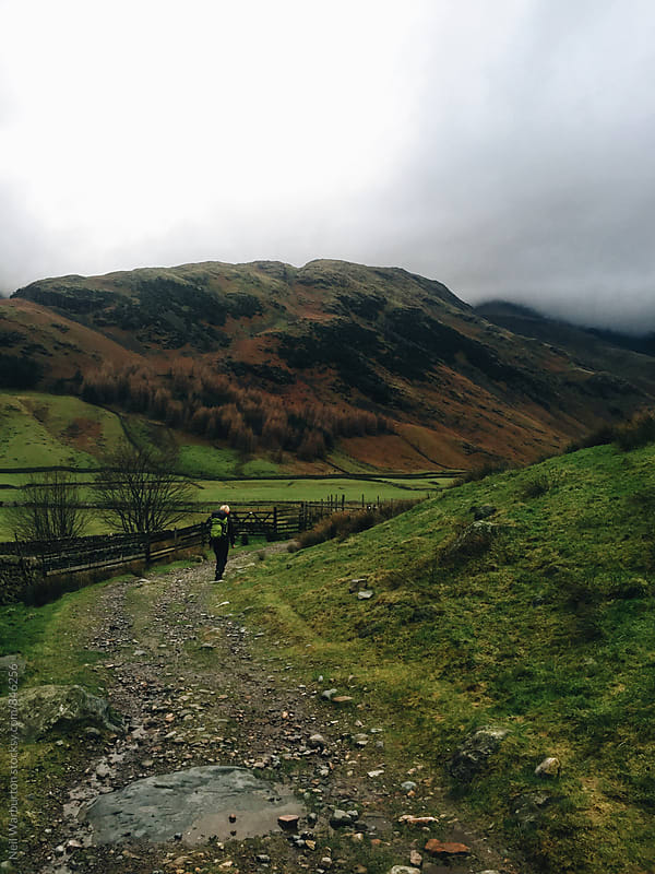 Hiker on a trail in a Lake District Valley by Neil Warburton for Stocksy United