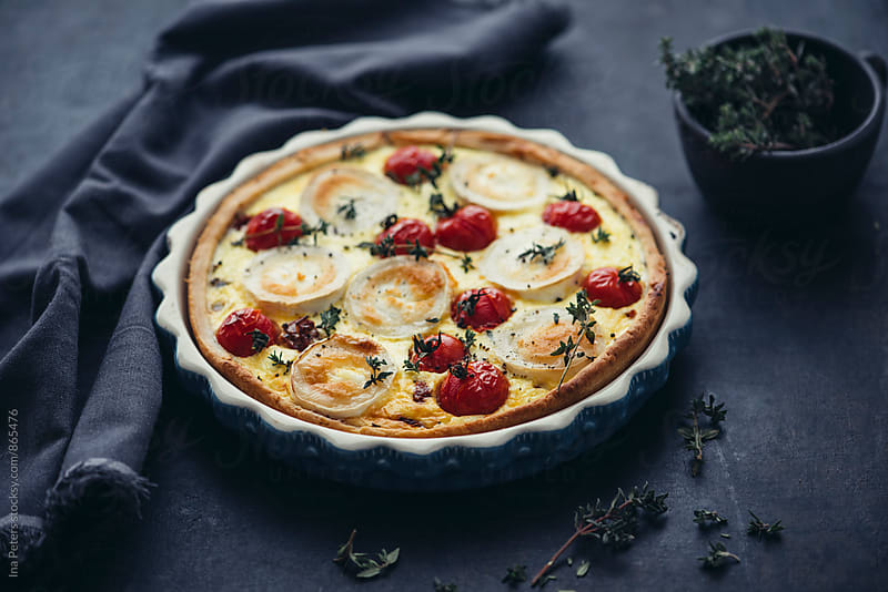 Food: Tomato and goat cheese quiche with thyme by Ina Peters for Stocksy United