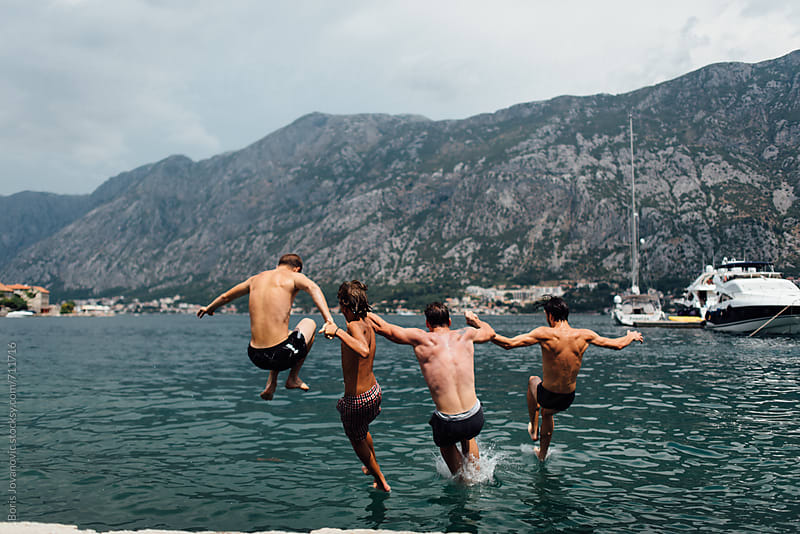 Four crazy friends jumping in sea by Boris Jovanovic for Stocksy United