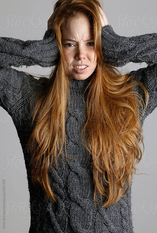 girl with long red hair blocking her ears for noise by Rene de Haan for Stocksy United