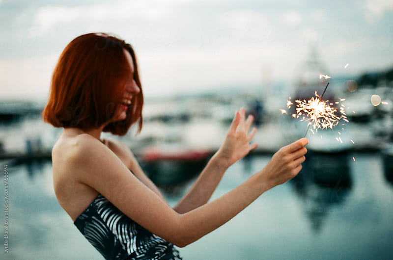 Young woman having fun with a sparkler by Lyuba Burakova for Stocksy United