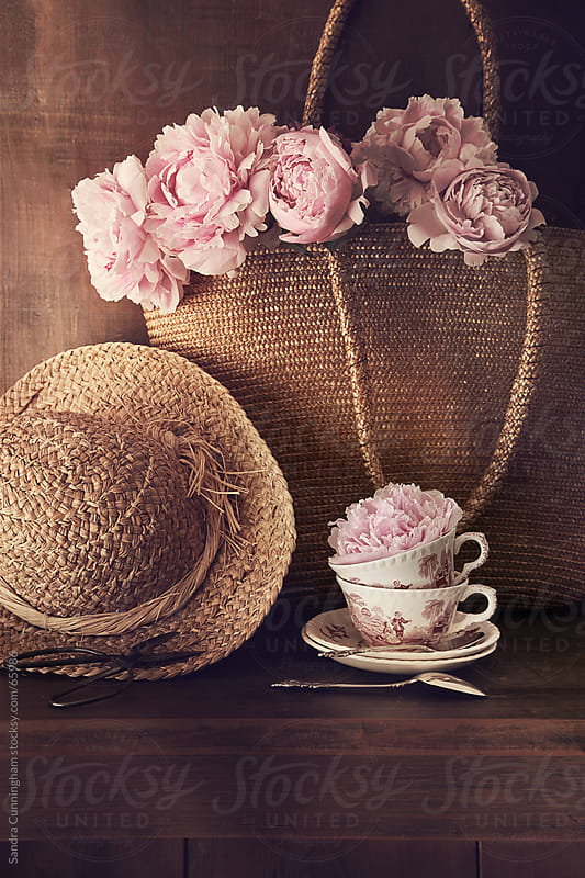 Freshly cut peonies with wicker hat and bag by Sandra Cunningham for Stocksy United