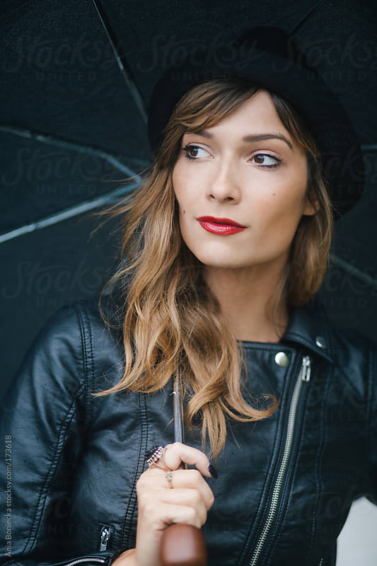Beautiful woman in a leather jacket standing in the rain by Ania Boniecka for Stocksy United