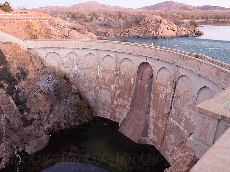 Lake with dam and icy water on one side by Jeremy Pawlowski for Stocksy United