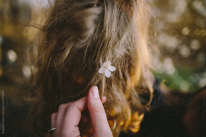 Hand reaching the flower in the blond hair by Evgenij Yulkin for Stocksy United