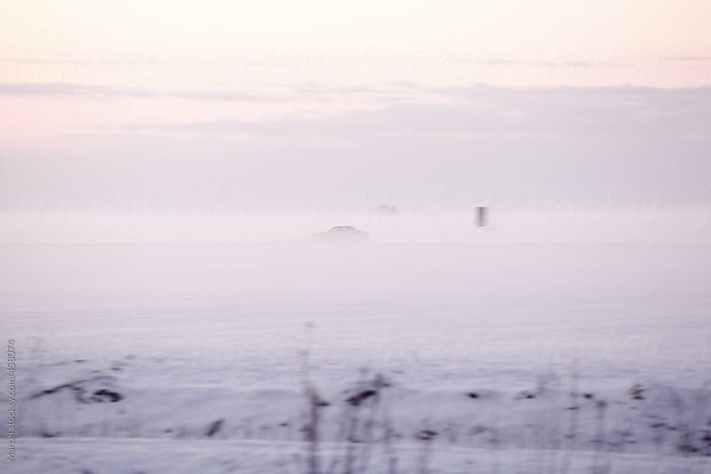 Car driving though dense fog at sunset on a cold winter day by Marcel for Stocksy United