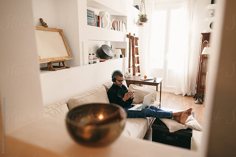 Man sitting on couch using smartphone at home. by BONNINSTUDIO for Stocksy United