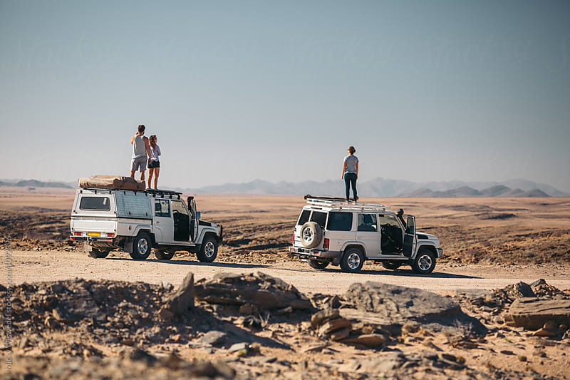Friend on top of their vehicles on a roadtrip in the desert by Micky Wiswedel for Stocksy United