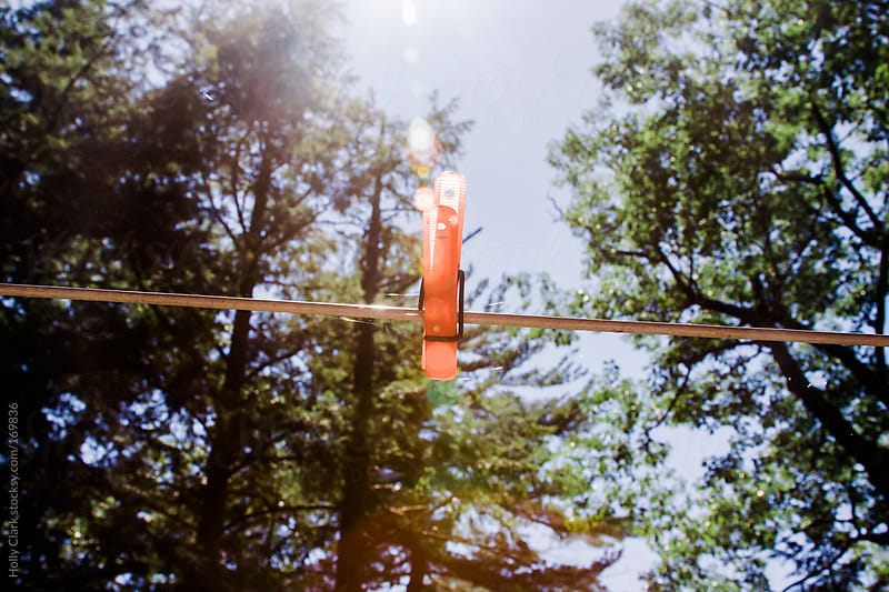 Summer sun shines down on an orange clothespin on a laundry line by Holly Clark for Stocksy United