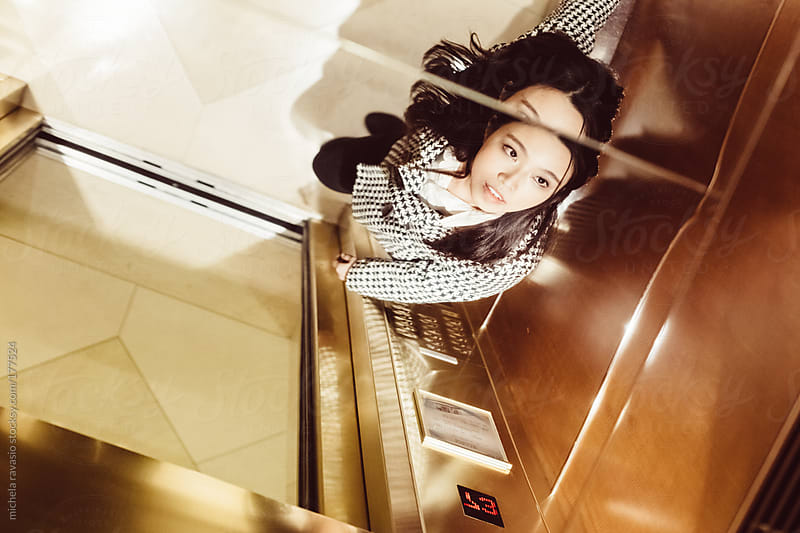 Young asian woman in the lift by michela ravasio for Stocksy United
