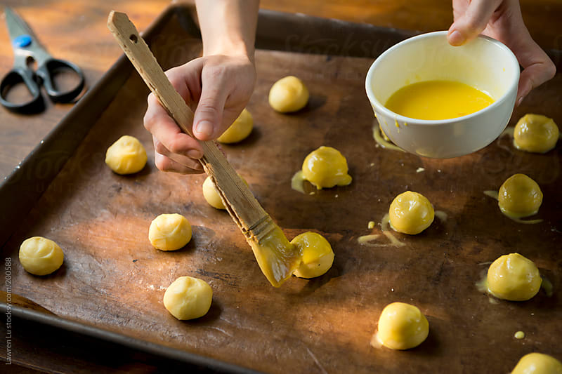 Woman hands brushing egg yolk for baking bread by Lawren Lu for Stocksy United