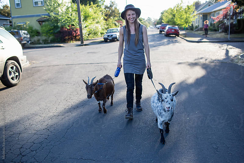 Young woman walking with her two goats by michela ravasio for Stocksy United