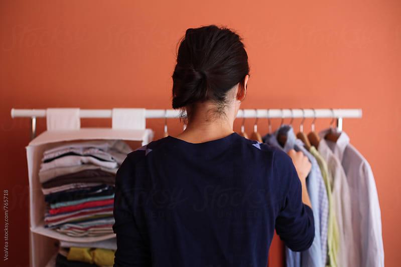 Woman choosing shirt in her room  by Marija Mandic for Stocksy United