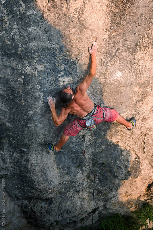 Strong man climbing a rock face outdoor at sunset by RG&B Images for Stocksy United
