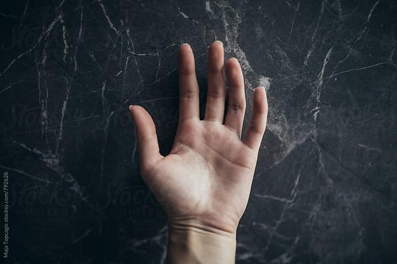 Female hand against a dark background by Maja Topcagic for Stocksy United
