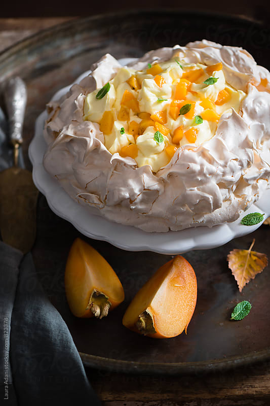 Pavlova with custard and persimmon on a cake stand by Laura Adani for Stocksy United