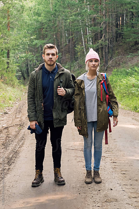 Couple of young backpackers on road in forest by Danil Nevsky for Stocksy United