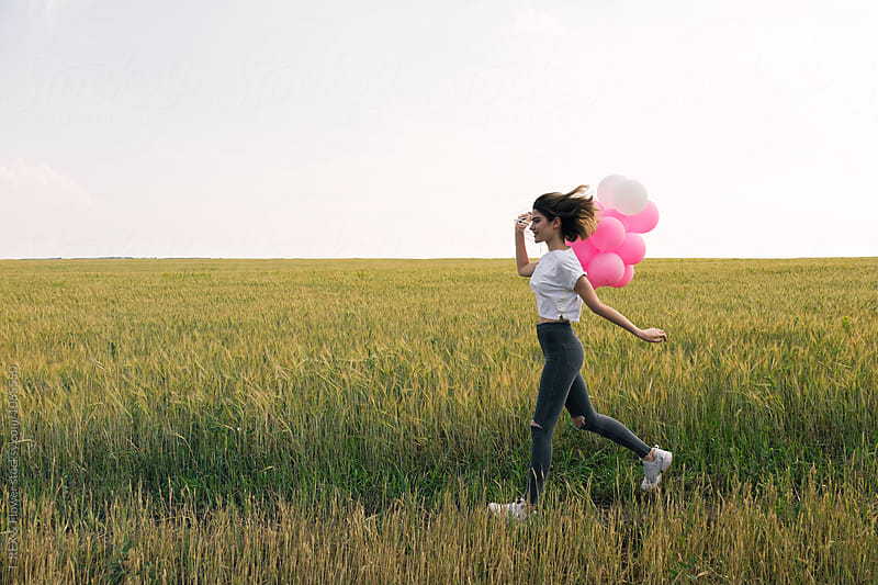 Happy young girl with air balloons running against of field by Danil Nevsky for Stocksy United