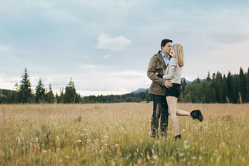 A young couple kissing in a field  by Ania Boniecka for Stocksy United