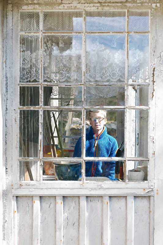 Young boy is looking out through an old window by Jonas Räfling for Stocksy United