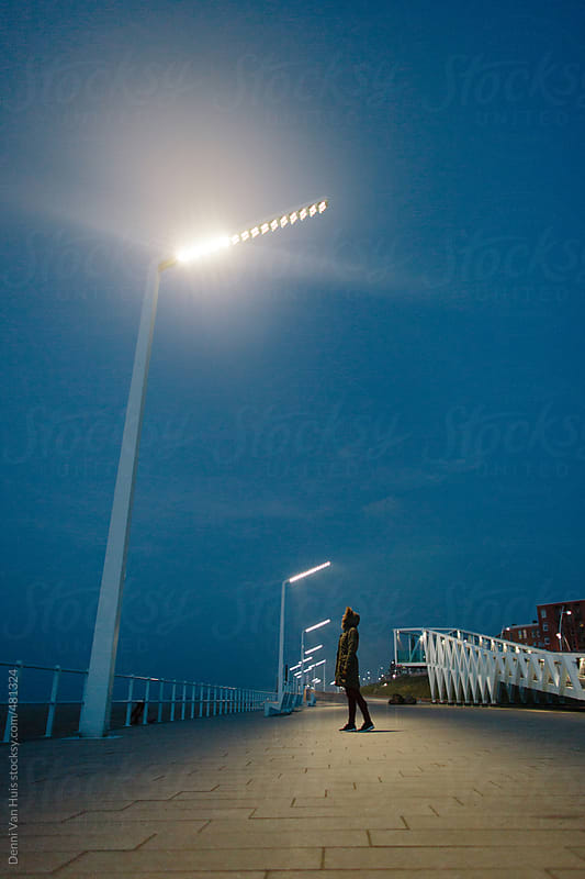 Lonely person standing in the dark looking up at a tall lamppost by Denni Van Huis for Stocksy United