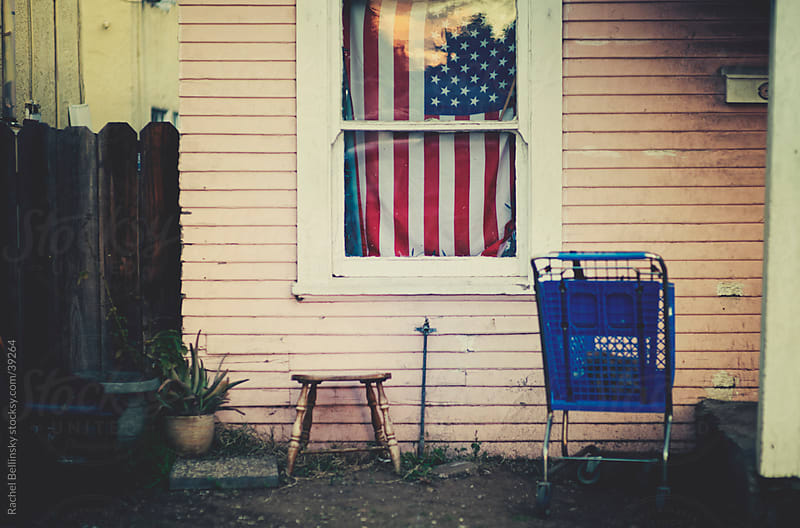 American flag and shopping cart on the porch of an old pink house by Rachel Bellinsky for Stocksy United