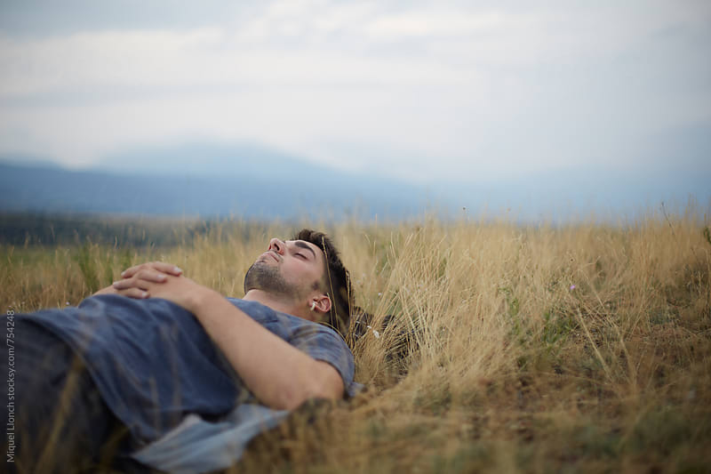 Young man laying and resting on the grass of a field by Miquel Llonch for Stocksy United