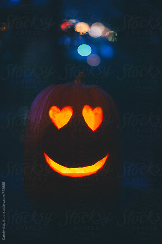 Happy Halloween pumpkin with glowing heart eyes by Carolyn Lagattuta for Stocksy United