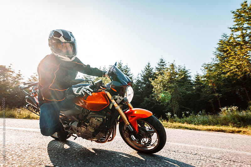 Man riding motorcycle by Dimitrije Tanaskovic for Stocksy United