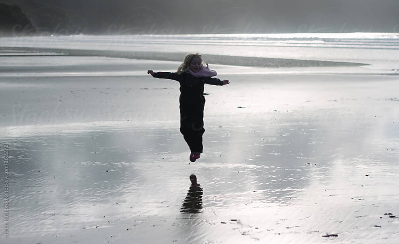 A little girl jumping on a beach in winter by Helen Rushbrook for Stocksy United