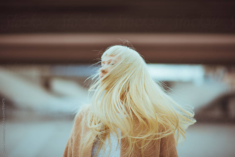 Blonde woman tossing her head to the side  by Drew Schrimsher for Stocksy United
