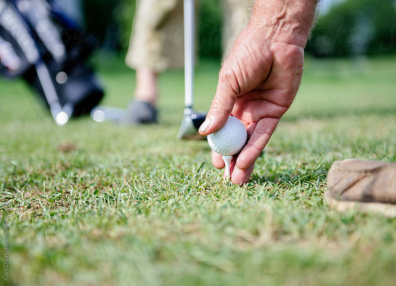 Man readies his golf ball on a tee by Cara Dolan for Stocksy United