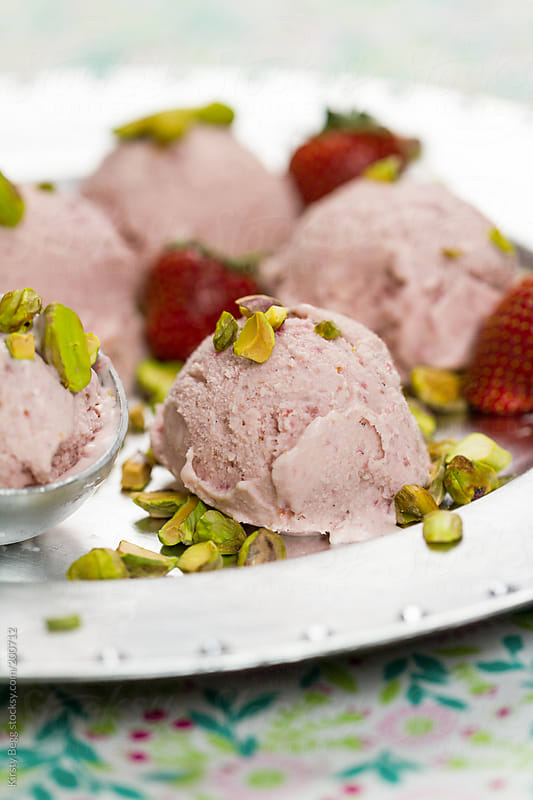 Scooped Strawberry ice cream with pistachio nuts by Kirsty Begg for Stocksy United