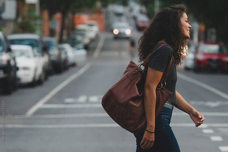 Young woman crossing the street in the city by Lauren Naefe for Stocksy United