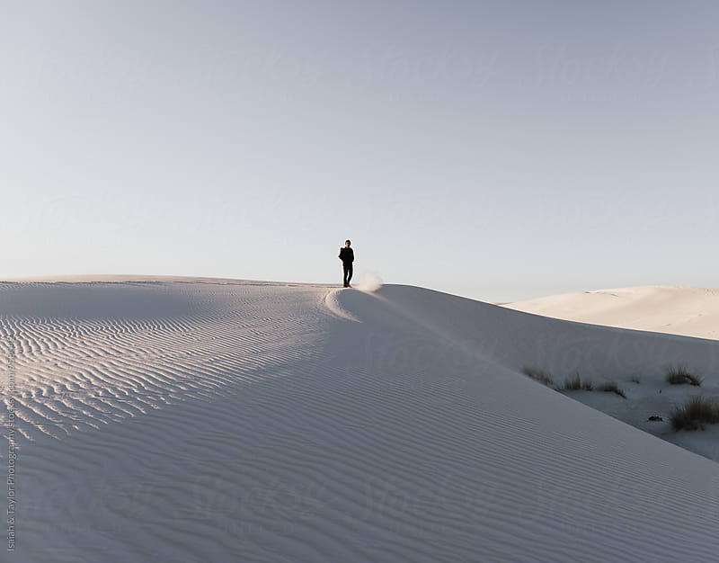 Man standing on sand dune by Isaiah & Taylor Photography for Stocksy United