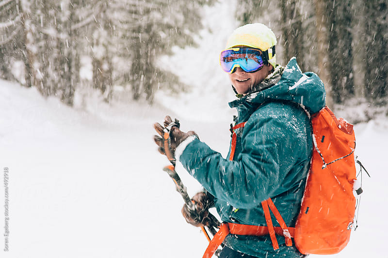 Happy smiling male skier in snow storm looking at the camera in the winter mountains by Soren Egeberg for Stocksy United