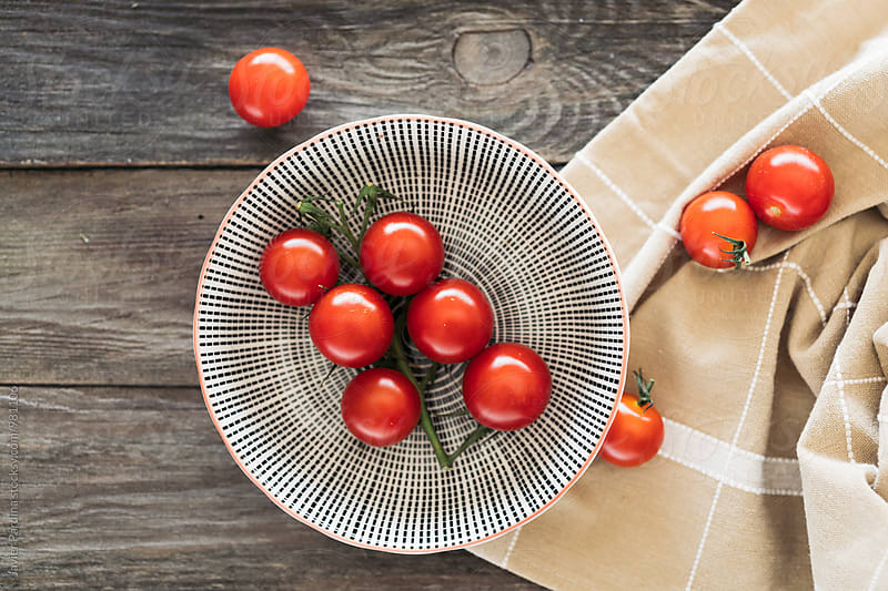 fresh tomates on the wooden table by Javier Pardina for Stocksy United