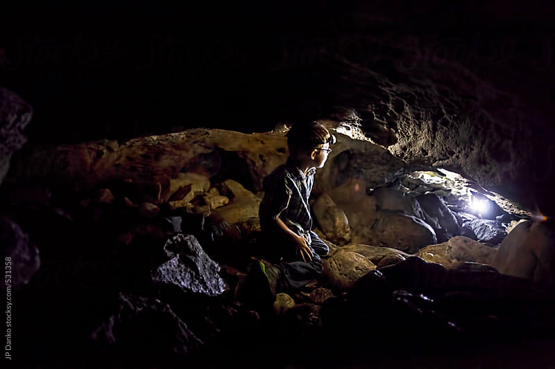 Little Boy Exploring a Dark Natural Cave With A Headlight by JP Danko for Stocksy United