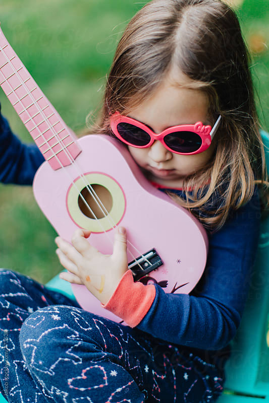 Cute young girl in sunglasses playing guitar outside by Jakob for Stocksy United