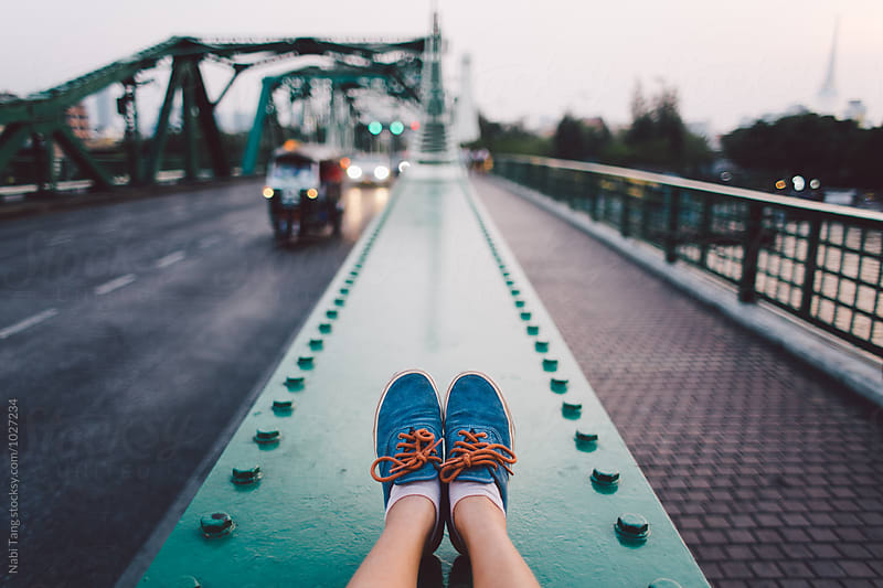 Woman making picture of her own feet while sitting on the bridge over the river in Bangkok by Nabi Tang for Stocksy United